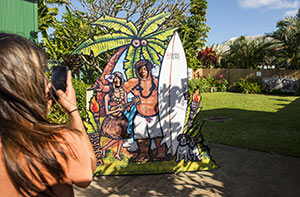 A family poses for the funny photo op at The Kong Lung Center, between Island Soap and The Kilauea Bakery.